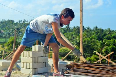 Vrijwilliger helpt de lokale bevolking door het renoveren en bouwen van huizen en scholen