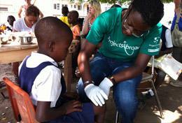 Help tijdens de geneeskunde groepsreis voor jongeren naar Ghana bij het verzorgen van wondjes van lokale kinderen.