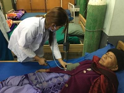 In Nepal luistert een vrijwilliger naar de hartslag van een patiënt tijdens de jongerenreis geneeskunde.