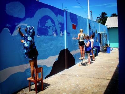 Vrijwilligers verven de muren in een kinderopvang tijdens de jongerenreis op het sociaal en samenlevingsproject Ecuador