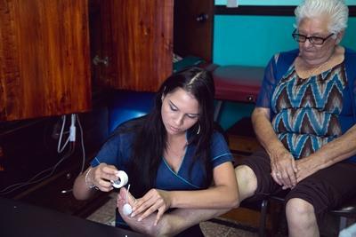 Een vrijwilliger verzorgt een patiënt in het centrum voor bejaarden op het fysiotherapie project in Samoa