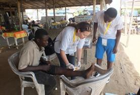 Public Health vrijwilligers assisteren bij het schoonmaken van wondjes tijdens een medical outrach in Togo.