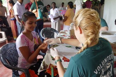 Projects Abroad vrijwilliger test de bloedsuikerwaarden en bloeddruk tijdens een outreach in Sri Lanka