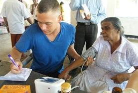 Een verpleegkunde vrijwilliger help een patient in Sri Lanka bij het meten van de bloeddruk.