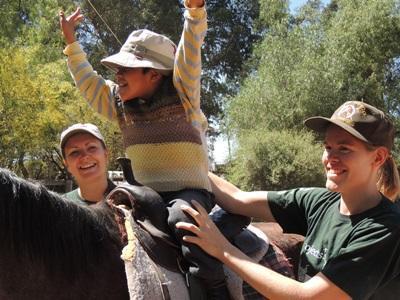 Vrijwilligers assisteren tijdens een therapiesessie op het paardentherapie project in Bolivia