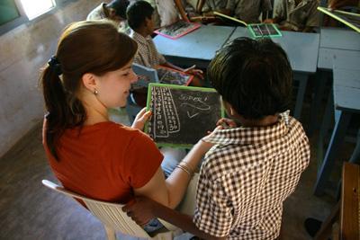 Projects Abroad vrijwilliger helpt een leerling in de klas op een lesgeef project in Bangladesh