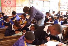 Als vrijwilliger op een lesgeef project in Kaapstad sta je voor de klas en help je de scholieren bij hun opdrachten.