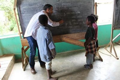 Een vrijwilliger van Projects Abroad geeft les aan de kinderen in een lokale school in Madagaskar