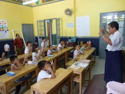 Kinderen krijgen les van een leraar in Myanmar