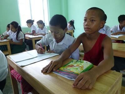 Een jonge monnik krijgt samen met de lokale kinderen onderwijs in een kloosterschool in Myanmar