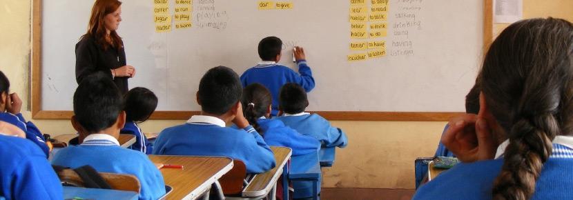 De vrijwilliger leert de kinderen de engelse taal