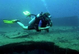 Een vrijwilliger doet onderzoek naar koraal tijdens het duiken voor het Natuurbehoud vrijwilligersproject in Thailand.