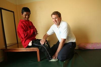 Een Projects Abroad vrijwilliger helpt een kind in Nepal met fysiotherapie oefeningen.