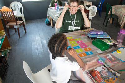 Een schoolkind in Belize krijgt hulp bij het leren van nummers van een professionele docent.