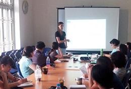 Een ervaren sociaal werker geef vrijwillig een presentatie aan lokale collega's in Vietnam
