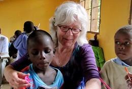 Een oudere vrijwilliger ondersteunt een kind tijdens vrijwilligerswerk in het buitenland.