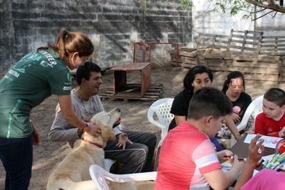 Vrijwilligers assisteren tijdens therapie sessies met honden in een centrum waar kinderen met beperkingen worden behandeld