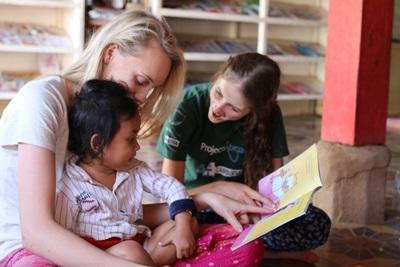 Op het Sociale zorg project in Cambodja helpen de vrijwilligers de kinderen met lezen