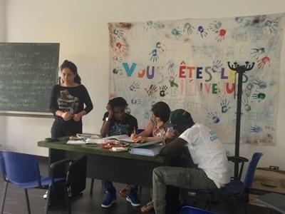 Vluchtelingen in een klaslokaal in Italië, waar vrijwilligers helpen bij het geven van Engelse les.
