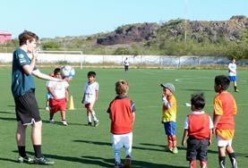 Een vrijwilliger bereid kinderen voor op een sportwedstrijd na schooltijd.