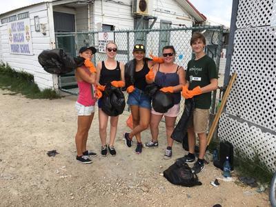 Vrijwilligers van het community sport project moedigen kinderen in Belize ook aan het strand schoon te houden.