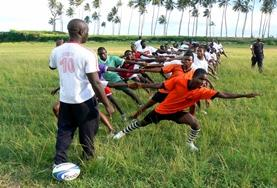 Een rugby vrijwilliger helpt bij de training van lokale spelers.
