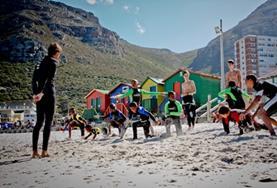 Een vrijwilliger op het surf project in Kaapstad geeft instructies aan de kinderen die willen leren surfen.