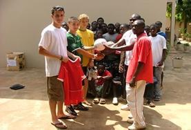 Vrijwilligers op het voetbal project maken een groepsfoto van hun team.