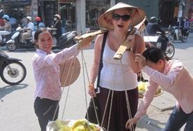 Een vrijwilliger brengt haar opgedane talenkennis van het Vietnamees in de praktijk op een markt.