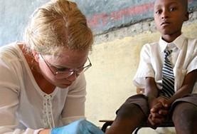 Help mijn bij de verzorging van wondjes tijdens de gezondheidszorg groepsreis voor vrijwilligers naar Kenia.