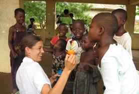 Een vrijwilliger van de groepsreis naar Ghana speelt met de lokale kinderen.